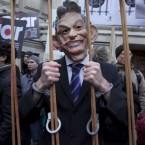 A protestor in a Tony Blair mask makes his point outside the London venue where the former British prime minister was giving his evidence to the Chilcot Iraq Inquiry today. Blair admitted he had diregarded legal advice that the invasion of Iraq without UN backing was illegal under international law. He said he regretted