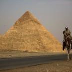An Egyptian man rides his camel as he looks for tourists next to Giza Pyramids after re-opening in Egypt. (AP Photo/Emilio Morenatti)