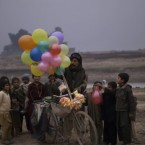 Pakistani children gather by a vendor on a bicycle selling balloons on the outskirts of Islamabad, Pakistan on Thursday.<span class=