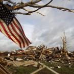 A flag hangs on a tree as tornado damage is seen in the background in Joplin, Missouri. (AP Photo/Jeff Roberson)
