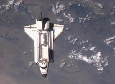 The space shuttle flies over the Earth in an image taken from the International Space Station
