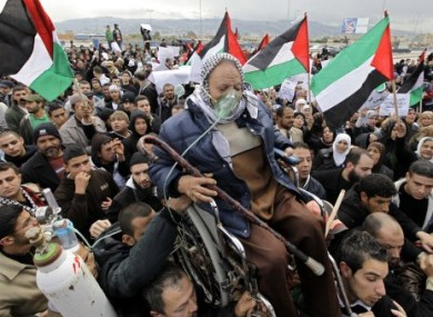 A Palestinian elder is held up among hundreds of Palestinians protesting in front of the UN relief agency, UNRWA, headquarters in Beirut, Lebanon, in March, concerned that the agency would drop services for Palestinian refugees.