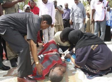 The president of Zanzibar, Ali Mohammed Shein, left, helps a survivor.