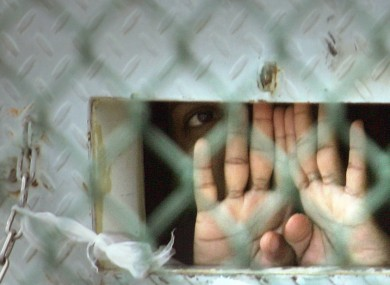 In this Dec. 4, 2006 file photo reviewed by the U.S. Military, a detainee peers out from his cell inside the Camp Delta detention facility at the Guantanamo Bay US Naval Base in Cuba.
