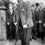 Manager Matt Busby still on crutches, as he arrives in Manchester from Munich, where he has been recovering from injuries sustained in the air disaster.