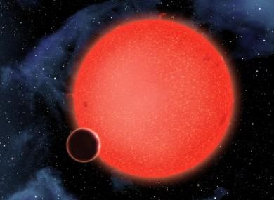 An artist's conception of GJ1214b orbiting a red dwarf star.