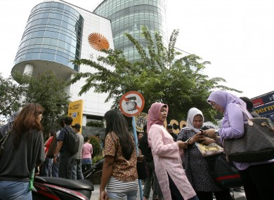 People wait as they are evacuated from a shopping mall after a strong earthquake was felt in Medan, Sumatra island, Indonesia.