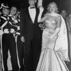 Actress Marilyn Monroe, escorted by her husband, playwright Arthur Miller, wears a big smile and waves to the crowd on arrival at the Radio City Music Hall in New York City, June 13, 1957. (AP Photo/Matty Zimmerman)