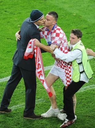 A Croatia fan runs on and kisses Croatia manager Slaven Bilic last night.