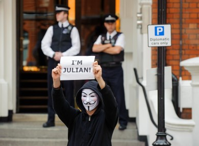 A masked supporter of Julian Assange outside the Embassy of Ecuador in London this afternoon