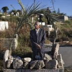 A Palestinian man visits a family member's grave outside Jerusalem's Old City as part of tradition during the first day of Eid al-Fitr. (AP Photo/Bernat Armangue/PA)
