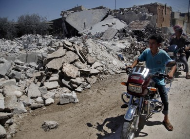 Syrians on motorcycles look at the damage of a destroyed house after it was hit by an air strike killing six Syrians in town of Tal Rifat on the outskirts of Aleppo city, Syria, Wednesday, Aug. 8, 2012