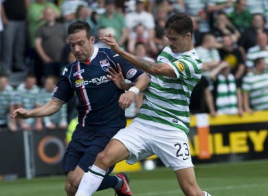 Ross County's Mark Corcoran holds off Celtic Mikael Lustig.