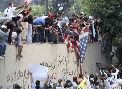 Protesters destroy an American flag pulled down from the US embassy in Cairo yesterday