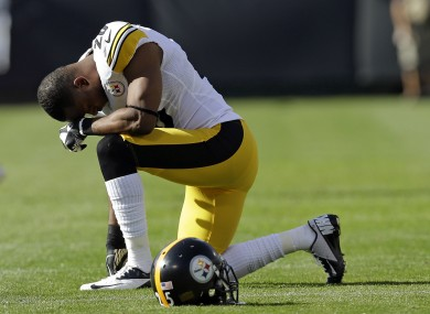Pittsburgh Steelers safety Ryan Clark kneels and waits following the injury to Oakland Raiders' Darrius Heyward-Bey.