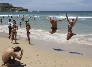 Beach goers jump in the air for a photo as they celebrate on Christmas Day at Bondi Beach in Sydney, Australia, Sunday, 25 December 2011