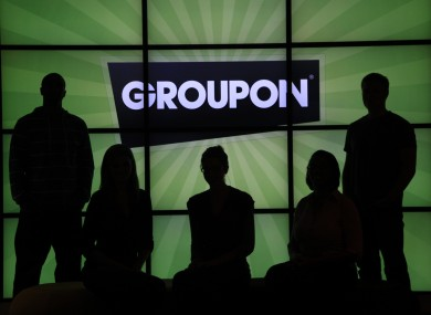 File: Employees at Groupon pose in silhouette by the company logo in the lobby of the online coupon company's Chicago offices.