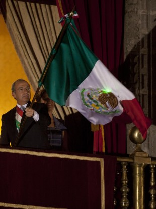 Felipe Calderon with the flag of Mexico or the United Mexican States as it's officially known, for now.