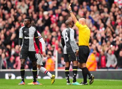 Tottenham Hotspur's Emmanuel Adebayor (l) is shown a straight red for a dangerous tackle on Arsenal's Santi Cazorla.