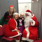 Louise Shorthall (7) with Santa Claus, Mrs Claus and their elf helper.