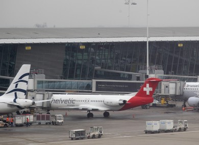 Baggage carts make their way past a Helvetic Airways aircraft from which millions' of dollars worth of diamonds were stolen on the tarmac of Brussels international airport.