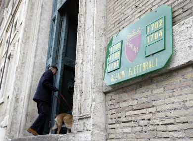 A man arrives to vote in a polling station in downtown Rome this morning.
