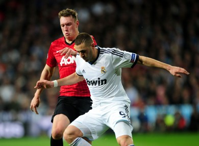 Manchester United's Phil Jones and Real Madrid's Karim Benzema (right) battle for the ball during the UEFA Champions League round of 16 match at Santiago Bernabeu.