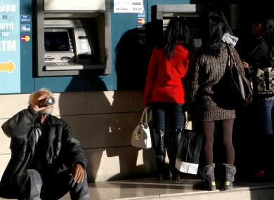 A man sits and drinks as women use the ATM outside of a Bank of Cyprus branch in Nicosia on Sunday