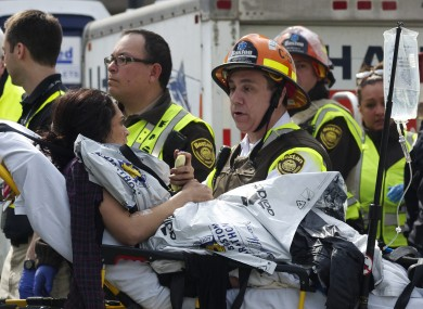 Emergency responders comfort a woman on a stretcher who was injured in a bomb blast near the finish line of the Boston Marathon.