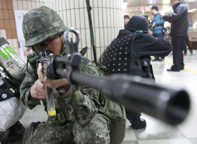A South Korean soldier aims a machine gun during a drill preparing for terrorist attacks in Seoul today
