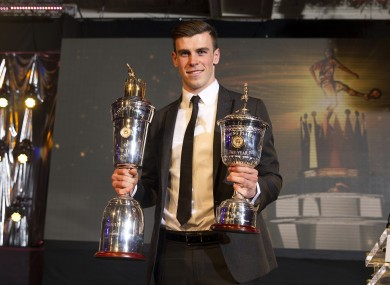 Gareth Bale holds his Young Player of the Year and Players' Player of the Year trophies during the PFA Player of the Year Awards 2013.