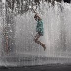 A youngster jumps in the midst of a fountain on the southbank of the River Thames in London. Temperatures reached 28 degrees Celsius (82 degrees Fahrenheit) in London on Monday. (AP Photo/Matt Dunham)