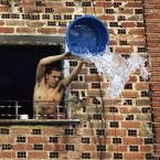 A man throws water over pedestrians during the 32th annual water fight in the streets of Vallecas, Madrid. (AP Photo/Andres Kudacki)