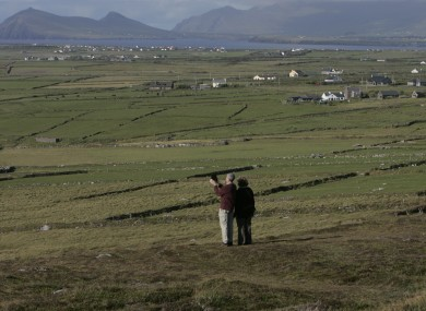 Tourists use their iPad to video the landscape as the Atlantic Ocean reaches land near Clogher Head on the Dingle Peninsula.