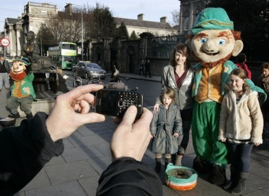 Ella Robins (4), Ava (8) and Leah (14) from Cork posing with a leprechaun near Trinity College Dublin.
