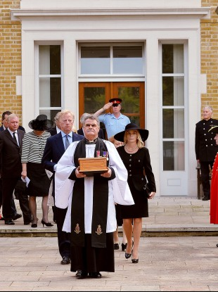 Reverend Richard Whittington carries an oak casket with the ashes of the former leader, followed by Thatcher's son Mark and his wife Sarah
