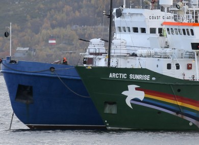 Russian coast guard boat, left, and the Greenpeace ship 'Arctic Sunrise', right, anchored next to it.