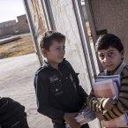 Twelve-year-old Abdo al-Fikri, left, arrives to school<span class=