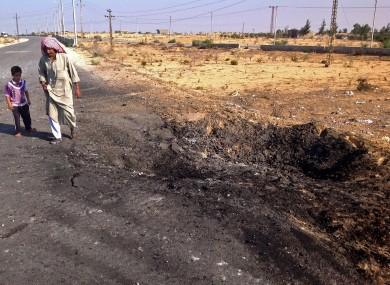 A man and child walk past the crater from the suicide car bomb attack.