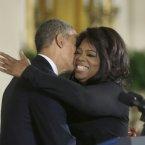President Barack Obama, left, kisses, Oprah Winfrey, before awarding the medal. <span class=
