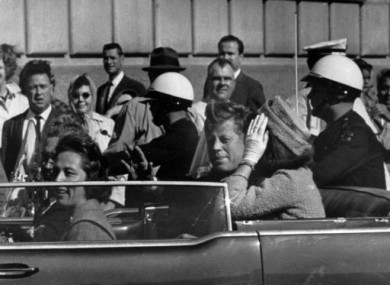 Kennedy rides in a motorcade with his wife Jacqueline, right, Nellie Connally, left, and her husband, Gov. John Connally of Texas