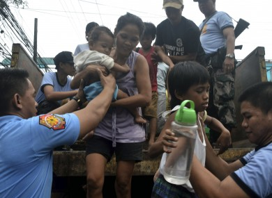 Residents living near the slopes of Mayon volcano are evacuated to public schools by police in anticipation of the powerful typhoon Haiyan