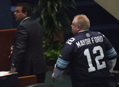 Ford chairs a meeting of Toronto City Council wearing a jersey of the local CFL franchise, the Toronto Argonauts. The team chided him for wearing the jersey.