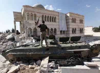 A Free Syrian Army soldier stands on a damaged Syrian military tank outside Aleppo