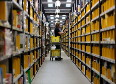 A worker selecting goods from racks in the Amazon fulfillment center in Peterborough, Cambridgeshire.