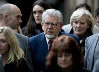 Rolf Harris, center, leaves amidst a group of people who accompanied him to his hearing at Southwark Crown Court in London.