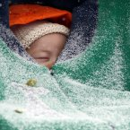 Two-month-old Jack Hsi takes a nap sheltered in his baby carrier while snow falls in Boston, <span class=