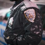 Snow accumulates on an NYPD officer in Times Square, in New York. <span class=