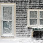 Ice from breaking waves coats a house along the shore in Scituate, Mass. A winter storm slammed into the U.S. Northeast with howling winds and frigid cold, dumping nearly 2 feet (60 centimetres) of snow in some parts and whipping up blizzard-like conditions Friday. <span class=