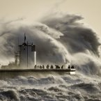 People watch and photograph enormous waves as they break on Porthcawl harbour, South Wales. <span class=